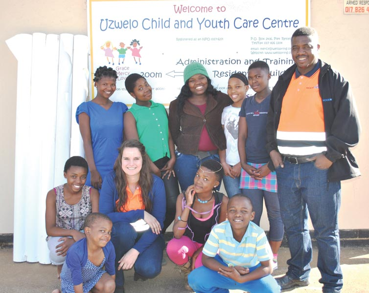 Mr John Mthimkulu en Mej Rachel Botha van Woodchemicals S.A. saam met die kinders van Uzwelo Youth and Child Care Centre