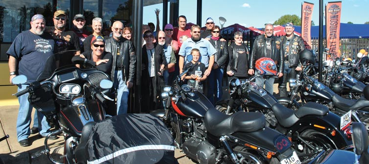 The HOG Big Five group members in front of Spur at their parked motorcycles