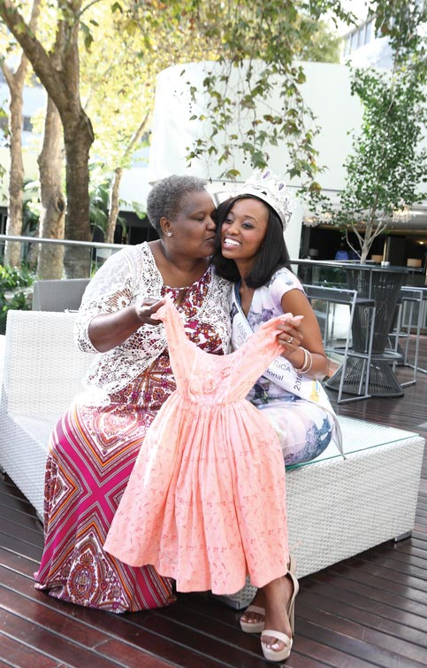 Nthandoyenkosi, wearing her Miss SA crown, with her mother, Mrs Baby Kunene, holding the dress she wore when clinching her first title