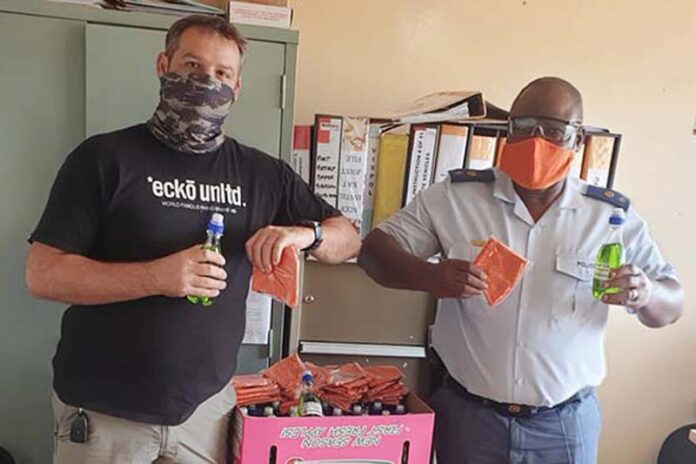 Mkhondo SAPS thankful. Gerhard Böhmer handing over the bottles of hand sanitizer and face masks to Lieutenant Colonel Blose of the Mkhondo SAPS